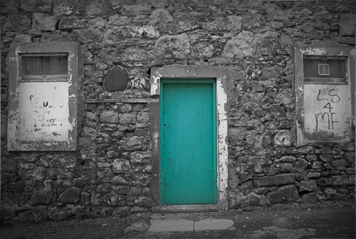 Black and white photograph with green door, selectively coloured